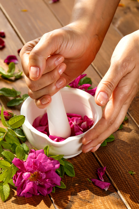 A pair of female hands holding a  mortar grinding rose petals