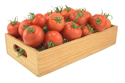 Tomatoes in a wooden box isolated on white